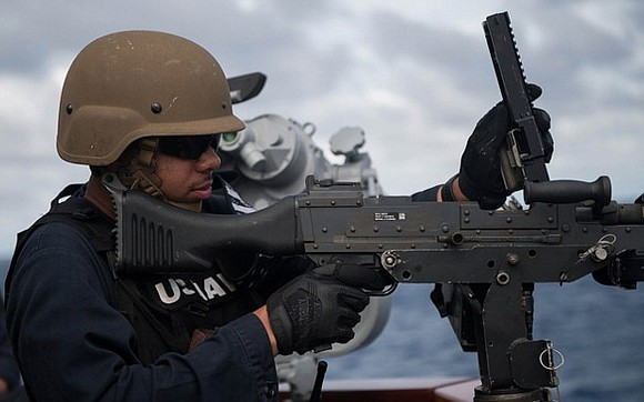 U.S. Navy Gunner's Mate 2nd Class Kimani Williams, from Houston, reloads an M240 machine gun during a live-fire exercise aboard ...