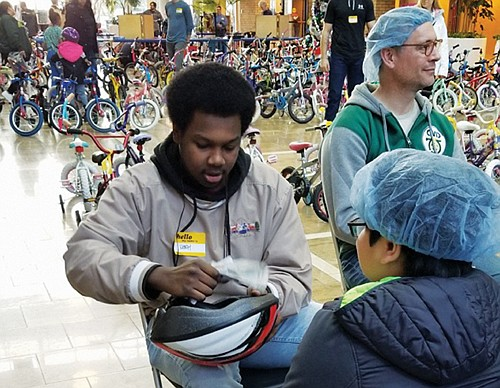 A young man gets some tips about bike helmet safety from trauma nurses at Legacy Emanuel Medical Center during the ...
