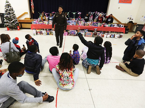 """Toys, toys, toys! Richmond Sheriff Antionette V. Irving talks with youngsters at the """"No Child Without a Toy"""" event last Friday at Woodville Elementary School in the East End. The city Sheriff's Office is partnering with St. Paul's Baptist Church and AFOI, Assisting Families of Inmates, to ensure that youngsters have gifts during this holiday season. The youngsters in AFOI's """"Milk and Cookies"""" mentoring program enjoyed face painting, decorating ornaments and other activities before the toys were distributed. The mentoring program is active in several Richmond elementary schools, including Woodville, Chimborazo and Swansboro. (Regina H. Boone/Richmond Free Press)"""