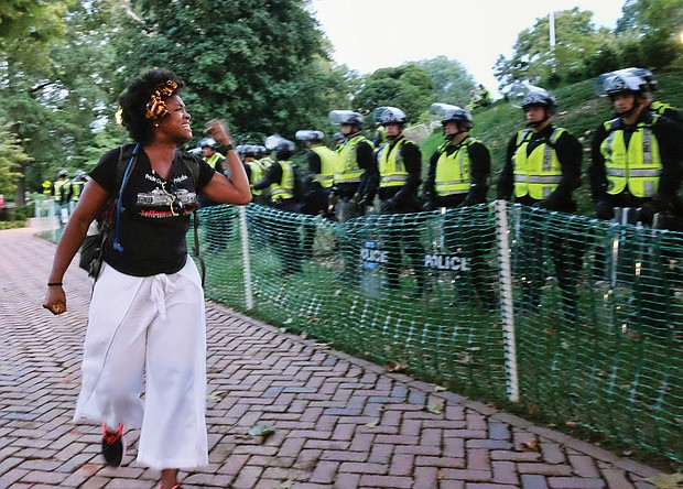 A University of Virginia student expresses her disgust at State Police who blocked off part of the Charlottesville campus in August in anticipation of protesters on the first anniversary of the 2017 white supremacist rally in the city in which one woman was killed and dozens of others were injured when a neo-Confederate drove his car into a crowd of counterprotesters.