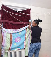 Kanya N. Nash puts blankets and quilts up at the windows to stave off January's cold in her apartment in the Hillside Court public housing community. She was among hundreds of public housing residents impacted by poor maintenance and the replacement of failed heating systems in buildings run by the Richmond Redevelopment and Housing Authority.