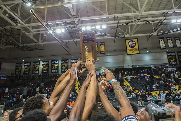 Jubilant John Marshall High School basketball players show off their 3A state championship trophy after their big victory in March over Western Albemarle High School at Virginia Commonwealth University's Siegel Center. This was the Justices first state championship since 2014.