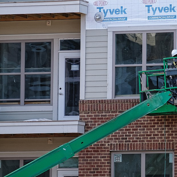 A worker puts siding on the new Artisan Hill apartment building that will have 204 units and underground parking last Saturday. Location: 1000 Carlisle St. (Sandra Sellars/Richmond Free Press)