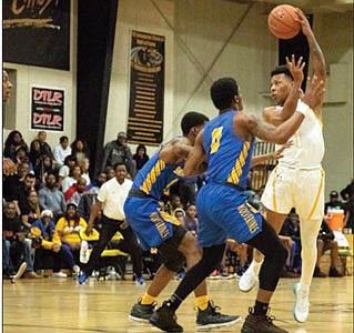 Saint Frances guard Adrian Baldwin makes a pass over two defenders from Chicago's Simeon Career Academy.