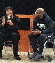 Keynote speaker Etan Thomas and his cousin William, discussing the power of fatherhood and family engagement before a crowd of fathers in the cafeteria of Frederick Douglass High School in West Baltimore