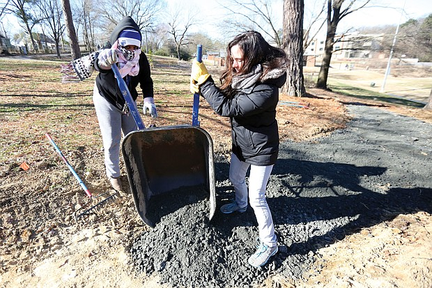 "Rachel Motley, left, and Erin Almquist of Richmond pitch in to care for a biking and walking trail at Bellemeade Park in South Side on Monday as part of the City of Richmond's ""In Pursuit of the Dream"" events."