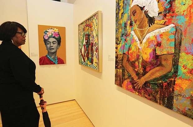 """Patricia Lancaster of Chesterfield County browses the work on view at """"The Art of Freedom"""" exhibit at the Black History Museum & Cultural Center in Jackson Ward. The exhibit, which is on view through May 19, includes more than 60 works in various mediums by 36 African-American artists born or living in Virginia who express their meaning of freedom."""