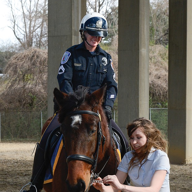 Whoa, Aslan!-Tori Branard makes a final adjustment to Aslan's bridle at the Feb. 7 badging ceremony inducting the horse into the Richmond Police Department's Mounted Unit. As a student at Asbury University's unique Service Mounts Program in Kentucky, Ms. Branard spent three years training Aslan, a Percheron-thoroughbred cross. Watching is Aslan's amused partner, Master Patrol Officer Amanda Acuff. Aslan is the fourth horse in the unit and is a replacement for Rio, who was retired in December. The others are Samson, Scooter and Toby. The horses live in a condemned stable near Gilpin Court. The police department is seeking other sources of funding for a new facility after recent bids to replace the current stable came in $1 million over budget. (Clement Britt)