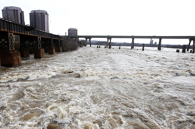 The still swollen James River is an awesome sight as it rushes Wednesday through Richmond's Downtown near the Federal Reserve Bank and Riverfront Towers. Still, the water was beginning to subside and had fallen below the 12-foot flood stage in this area by the afternoon, according to the U.S. Geological Survey, which keeps close track of the flow. On Tuesday, the river had risen to more than 16 feet as it passed through the area, fueled by weekend rains in the western part of the state. The city, which is protected by a floodwall in much of its Downtown, did not report any significant disruption or damage from the high water. (Regina H. Boone/Richmond Free Press)
