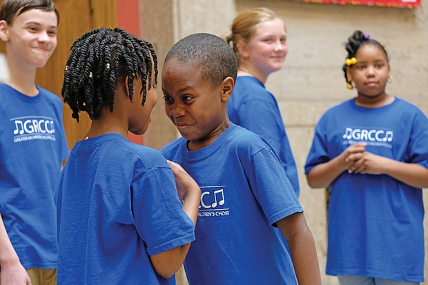 """No laughing matter- It looks like a stare down. But youngsters in the Greater Richmond Children's Choir were performing """"No Laugh Race"""" on Saturday, a song interspersed with a challenge requiring two people to stare at each other without laughing. The first one to laugh loses. The choir also engaged members of the audience in the performance. (Sandra Sellars/Richmond Free Press)"""