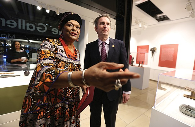 """'Unbound 2019: Truth & Reconciliation': In one of his first public appearances since the blackface scandal, Gov. Ralph S. Northam, guided toward the artifacts by Delegate Delores L. McQuinn of Richmond, chair of the commission, attend the opening of """"Unbound 2019: Truth & Reconciliation"""" on Feb. 28, at The Gallery at Main Street Station. This is the first part of a yearlong exhibition launched by the Richmond Slave Trail Commission to tell the stories of Africans in the Americas before 1619 through the present day. Located on the first floor, the exhibition is open to the public without charge 8 a.m. to 5 p.m. daily at the station, 1500 E. Main St. Under Gov. McDonnell's administration, the state put up $11 million for various historical projects related to memorializing the enslaved in Virginia, including the Lumpkin's Jail site and a related museum in Shockoe Bottom and funds for the improvement of the Richmond Slave Trail. (Regina H. Boone/Richmond Free Press)"""