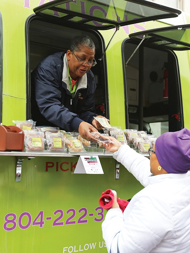 """'Mobile Soul Sunday'':Teresa Rogers leans out of the window of her food truck business, Sweet Temptations by Teresa, to sell a sweet treat to Evangeline Wood of Ashland on Sunday on Hull Street. Ms. Rogers' food truck was among 15 in South Side for """"Mobile Soul Sunday,"""" the kickoff of the 2019 Richmond Black Restaurant Week Experience. The event, which runs through Sunday, March 10, highlights Richmond's black-owned restaurants, food truck and cart operators, caterers and local chefs. (Regina H. Boone/Richmond Free Press)"""