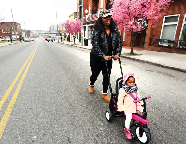 On a roll: Shamika Robinson and her 18-month-old daughter, Londyn Bryant, head toward the delicious smells of food coming from a bevy of food trucks Sunday on Hull Street in South Side. The food truck rodeo kicked off the 2019 Richmond Black Restaurant Experience. Children's games also were part of the festivities. (Regina H. Boone/Richmond Free Press)