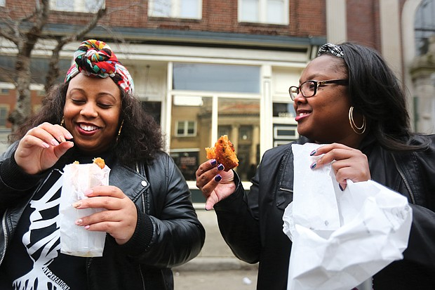 """""""Mobile Soul Sunday,"""" the kickoff of the 2019 Richmond Black Restaurant Week Experience which runs through Sunday, March 10, highlights Richmond's black-owned restaurants, food truck and cart operators, caterers and local chefs. Kelli Hughes and Mica Younger enjoy steak egg rolls from RVA Steak. (Regina H. Boone/Richmond Free Press)"""