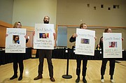 """Activists with the group """"Disarm PSU"""" demonstrate during a break at a Portland State University Board of Trustees Meeting Thursday. They read the names of people killed on college campuses across the country, chanting """"Jason Washington, say their names! Disarm PSU! Disarm PSU!"""""""