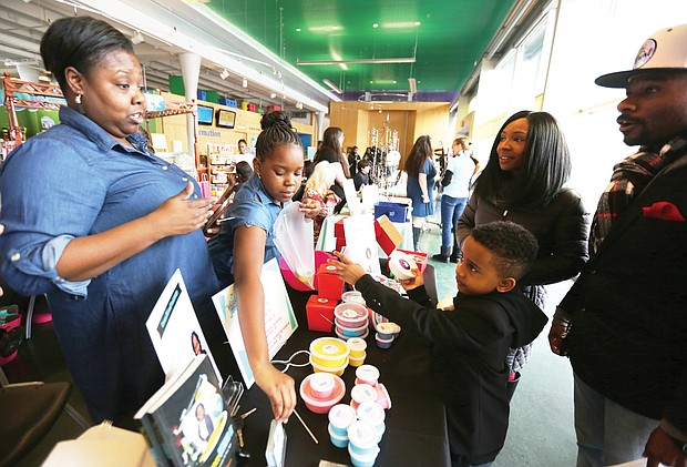 "Young entrepreneurs: More than 60 young entrepreneurs who created a variety of products showed off their wares and services during the 2nd Annual Richmond Children's Business Fair last Saturday at the Children's Museum of Richmond on West Broad Street near Downtown. Desiayah Dean, 11, of Newport News, second from left, makes and sells her own ""slime."" Her creation catches the attention of 7-year-old Chase Fisher Jr. of Richmond, who attended the fair with his parents, Ulani and Chase Fisher. Desiayah's mother, Rossie Dean, helps her with the sale. (Regina H. Boone/Richmond Free Press)"