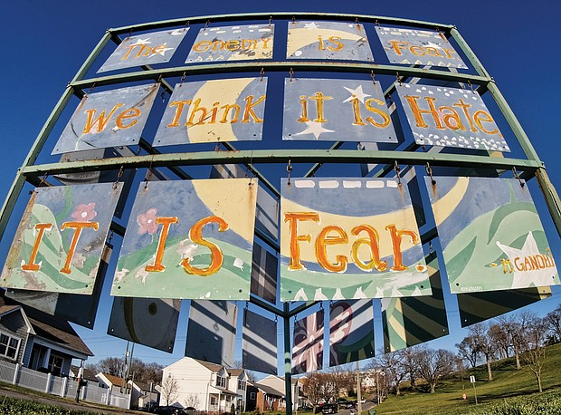 """Large, triangular public art stands on the future site of the Historic Fulton Memorial Park at 5001 Williamsburg Road at the foot of Powhatan Hill in the East End. The main element of the unsigned work is a quote from Mahatma Gandhi: """"The enemy is fear. We think it is hate; it is fear."""" (Sandra Sellars/Richmond Free Press)"""