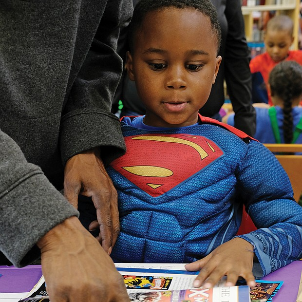 Young Superman/ Jaxson Snowden, aka Young Superman, checks out other superheroes with the help of the greatest superhero of all, his dad, T.J. Snowden, at the Chesterfield Comic Con last Saturday at the Chesterfield County Public Library's Meadowdale Branch. (Sandra Sellars/Richmond Free Press)