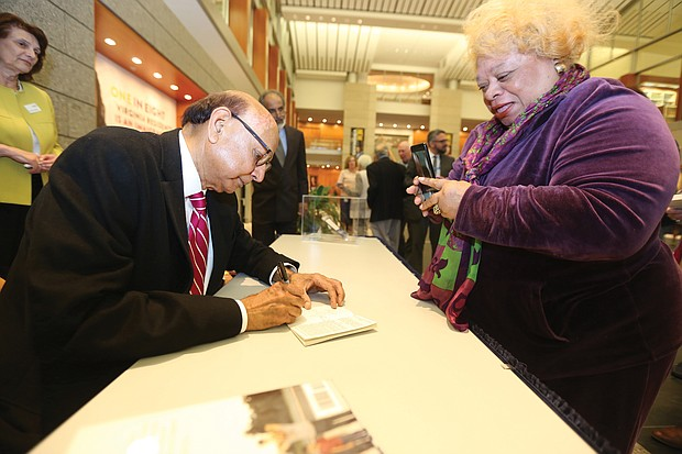 """An American story: Khizr Khan of Charlottesville, the father of a U.S. Army captain killed in Iraq in 2004, talked about his new book, """"An American Family: A Memoir of Hope and Sacrifice. He appeared April 4 at the Library of Virginia in Downtown as part of the 2019 Carole Weinstein Author Series. He signs a copy of his book for Dr. Paige L. Chargois of Richmond. (Regina H. Boone/Richmond Free Press)"""