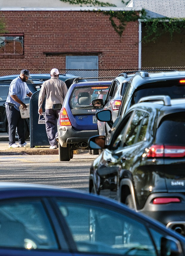 A line of motorists hurry to drop their 2018 federal income tax paperwork in the mail Monday by the tax filing deadline. The anxious drivers, photographed here about 6 p.m. Monday at the Main Post Office on Brook Road, were trying to ensure their envelopes received an April 15 postmark to avoid being hit with a penalty for missing the deadline. (Sandra Sellars/Richmond Free Press)