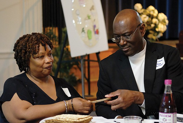 "People from many different faiths and backgrounds participate in an interfaith Passover ""Justice Seder"" Monday evening, using the Exodus story and Passover rituals to shine a light on modern-day oppression of racism, sexism, militarism and materialism. The event was held at Temple Beth-El on Grove Avenue. Above, Giselle Johnson and Tony Lamb break a piece of matzah during the Seder. (Sandra Sellars/Richmond Free Press)"
