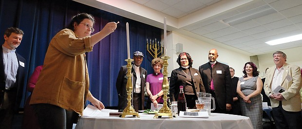 "People from many different faiths and backgrounds participate in an interfaith Passover ""Justice Seder"" Monday evening, using the Exodus story and Passover rituals to shine a light on modern-day oppression of racism, sexism, militarism and materialism. The event was held at Temple Beth-El on Grove Avenue. Above, Miriam Aniel of Richmond Jews for Justice conducts the candle lighting as other faith leaders look on. (Sandra Sellars/Richmond Free Press)"