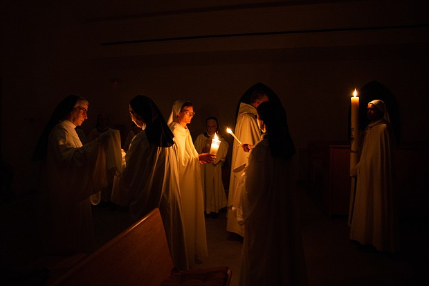 Nuns and guests at Our Lady of the Angels light candles during Easter Vigil Mass at the monastery in Crozet.