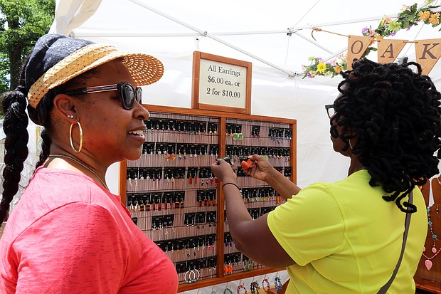 Shopping for wearable art: Dacia Henry, left, and Pat Smith of Richmond peruse earrings made by artist Shirley Hellms of Bremo Bluff during the 48th Annual Arts in the Park last Saturday. More than 450 artists from around the country showed off their work, which was for sale, during the event at the Carillon at Byrd Park. The show is sponsored by the Carillon Civic Association, and attracts painters, potters, photographers, jewelers and other craftspeople. (Regina H. Boone/Richmond Free Press)