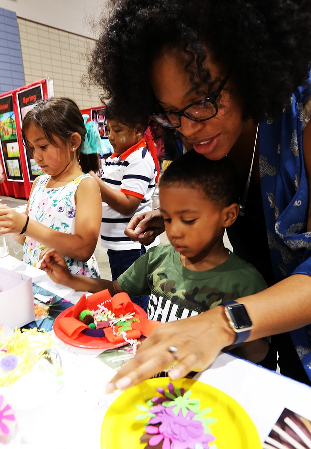 """Celebrating Asian-American culture: Last Saturday the 22nd Annual Asian American Celebration featured food, music, performances, exhibits, games and educational crafts from a variety of Asian nations. Marcus Brown Jr., 4, and his mother, Lesli Brown, work on creating an Indonesian flower offering called a """"Ganang Sari"""" at the Indonesian cultural activity booth during the festival. (Regina H. Boone/Richmond Free Press)"""