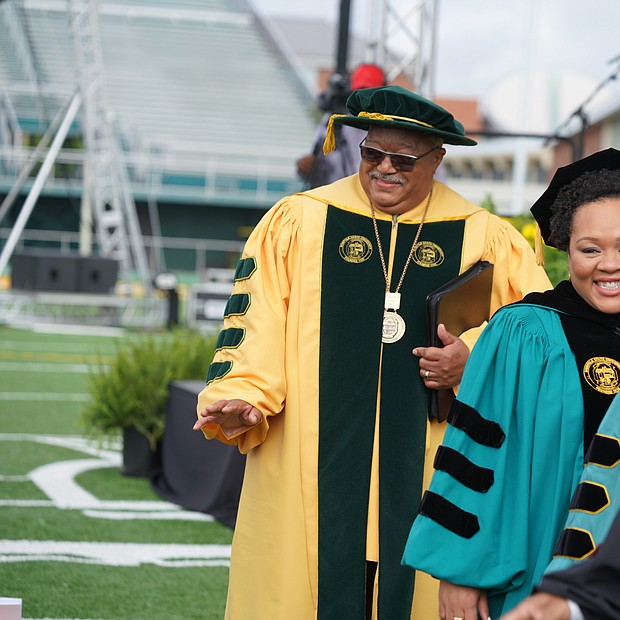 Behold the green and gold! Journalist Yamiche Alcindor, second from left, walks in Norfolk State University's 104th Commencement procession last Saturday at Dick Price Stadium on the Norfolk campus with NSU Interim President Melvin T. Stith, left. Ms. Alcindor, White House correspondent for PBS NewsHour, was the commencement speaker during ceremonies at which nearly 500 students were awarded undergraduate or advanced degrees. Members of the 50th reunion Class of 1969 were recognized during the ceremony. The Class of 1969 was the first to graduate from Norfolk State College, which became an independent institution of higher education on Feb. 1, 1969. Dr. Javaune Adams-Gaston, a senior vice president at Ohio State University, is expected to take over as NSU's seventh president in June. (Randy Singleton)