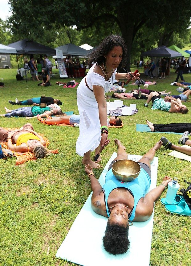 Shanna Latia of Richmond, standing at right, a trained yoga and Himalayan sound bowl therapist, helps Candace Benn of Chester feel the vibrations from the handcrafted Tibetan bowl during the 3rd Annual Peace Love RVA Yoga Festival last Saturday at Maymont. The free festival highlighted the growing yoga community in Richmond and urged compassion and love for all through a full day of free yoga classes and meditation led by area instructors. Music, vegetarian fare and local merchants also were featured, including musician Julian Desta of Richmond, below, who played a didgeridoo. (Regina H. Boone/Richmond Free Press)