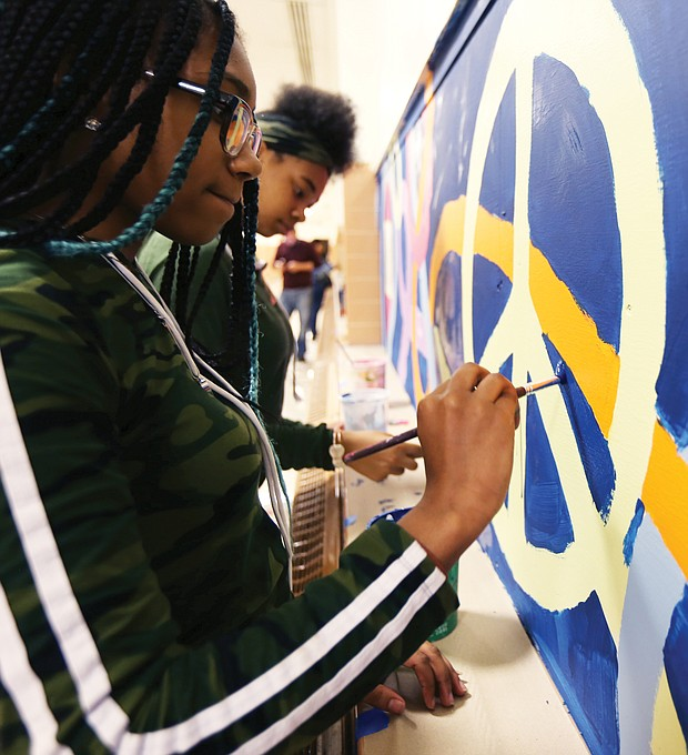 """Speaking through art/John Marshall High School students Denaisja Jones, 16, left, and Nikisha Flemming, 15, put finishing touches on a 13-week mural project at the North Side school titled, """"The Voices of John Marshall."""" The students participate in ART180's after-school community program, with the mural designed and created by 15 students with the co-leadership of local artist-volunteers Austin """"Auz"""" Miles and Justice Dwight. It is one of 16 projects ART180 has throughout the city. (Regina H. Boone/Richmond Free Press)"""