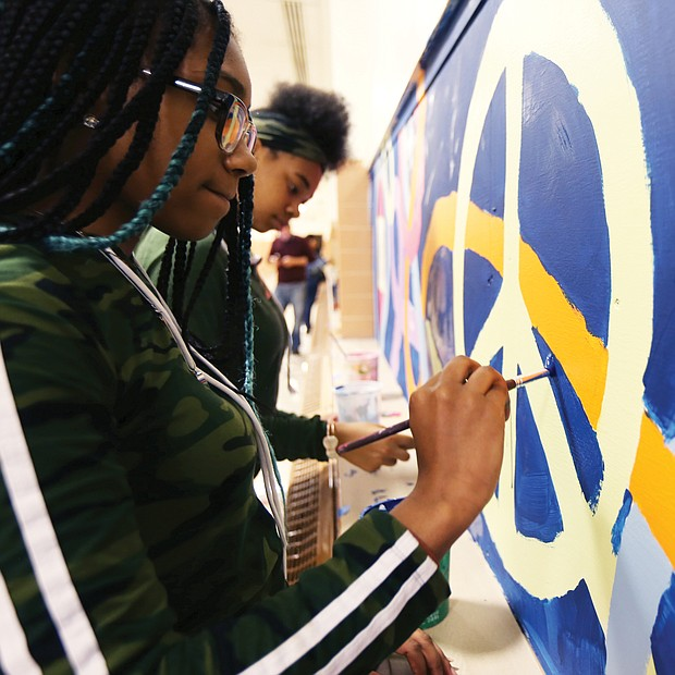 "Speaking through art/John Marshall High School students Denaisja Jones, 16, left, and Nikisha Flemming, 15, put finishing touches on a 13-week mural project at the North Side school titled, ""The Voices of John Marshall."" The students participate in ART180's after-school community program, with the mural designed and created by 15 students with the co-leadership of local artist-volunteers Austin ""Auz"" Miles and Justice Dwight. It is one of 16 projects ART180 has throughout the city. (Regina H. Boone/Richmond Free Press)"