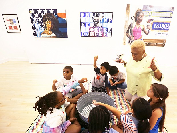 """Bookworms and history buffs/ Richmond School Board member and former principal Cheryl L. Burke leads an activity about acts of kindness Monday for second-graders from G.H. Reid Elementary School during the Black History Museum & Cultural Center of Virginia's Children's Book Festival. The event included the reading of """"Each Kindness,"""" a book by Jacqueline Woodson, tours of the museum's galleries and other activities. Each student was sent home with a bag of books at the end of the day. (Regina H. Boone/Richmond Free Press)"""
