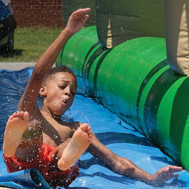 Splashing into the season/ Evan Mayfield, 10, whipped down the water slide Saturday at the 3rd Annual Cookout for a Cause at Westover Hills Elementary School in South Side. The free event, sponsored by Feed the Streets RVA, featured games, arts and crafts, bounce houses, food, music and other activities and vendors for youngsters and families to enjoy. Organizers asked only that each person bring a nonperishable food item to support FeedMore, Central Virginia's hunger relief organization. Evan, who enjoyed the cool water on a hot day with other young people, attended the event with his mother, Deborah Perry, and his sister, Kaelyn Davis, and her friend, Anna Zohore. (Sandra Sellars/Richmond Free Press)