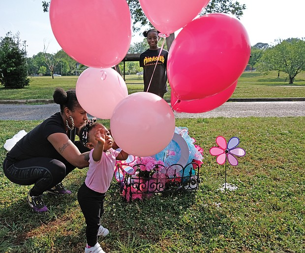 Marquita Ridley, left, and her daughters, Nyirah Phillips, 10, and Blessyn Evans place balloons Wednesday on a memorial at Carter Jones Park in South Side, where 9-year-old Markiya Dickson was fatally shot on May 26. Markiya's family is hosting a vigil at the park on Bainbridge Street at 5:30 p.m. Thursday, June 6