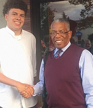 """Madison High School graduate Taj Ali (left) is congratulated for becoming the Valedictorian of his Class of 2019, the highest-scoring senior academically, from long time educator and mentor Michael """"Chappie"""" Grice."""