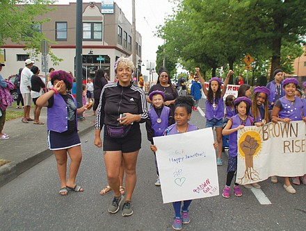 Members of the community group Brown Girl Rise participate in Saturday's annual Juneteenth Parade on Northeast Martin Luther King Jr. Boulevard.