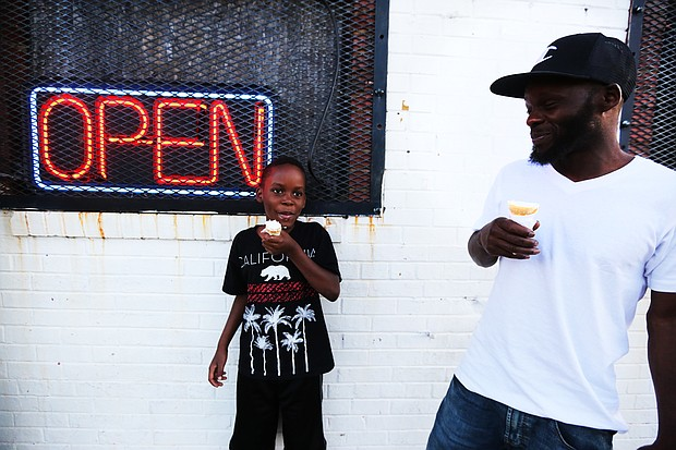 """'In The Sun Again' At the Robinson Theater Community Arts Center's """"In The Sun Again Community Block Party"""" last Friday at the Church Hill center, Jameer Dickerson, 8, and his dad, Ken Dickerson, enjoy ice cream cones at the party. The block party continues the theater's efforts to be a place that creates connections between residents and supports diversity and inclusion."""
