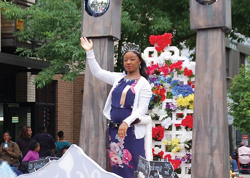 Rose Festival Queen Mya Brazile greets members of her community.