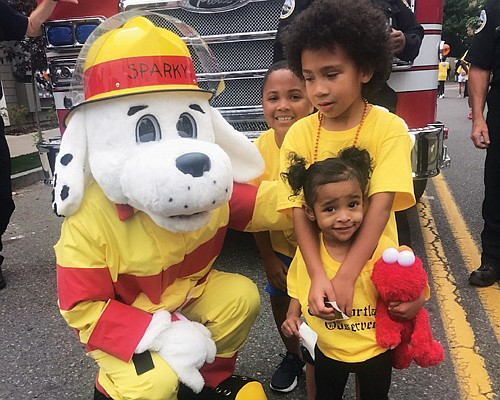 Portland Fire mascot Sparky has a big hello for young Good in the Hood Parade participants Deandre Perez, Jamar Tarver and Korie Washington Ta.