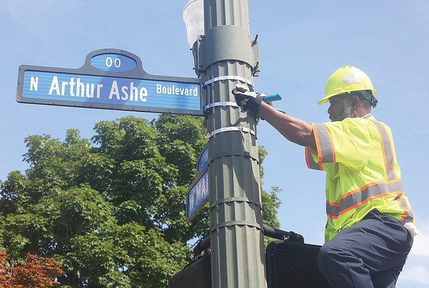 Richmond Department of Public Works employee Malik Mujahid installs one of the many new Arthur Ashe Boulevard signs at the renamed thoroughfare's intersection with Main Street following the official dedication ceremony. (Sandra Sellars/Richmond Free Press)