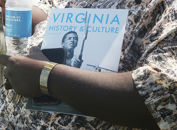 """A guest at the official dedication of Arthur Ashe Boulevard holds a water bottle and brochure about Arthur Ashe Jr., who is part of the Virginia Museum of History & Culture's current exhibit, """"Determined: The 400-Year Struggle for Black Equality."""" (Regina H. Boone/Richmond Free Press)"""