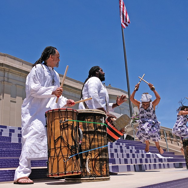 """Members of the Elegba Folklore Society perform during the dedication ceremony, with founder Janine Bell explaining to the crowd how the sound of the drums open the road — the new Arthur Ashe Boulevard — """"to let the people come forward."""" (Sandra Sellars/Richmond Free Press)"""