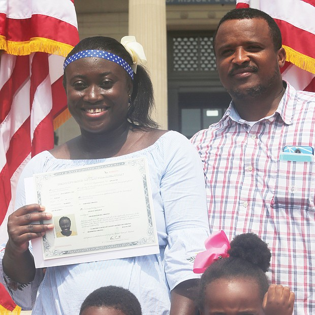 New U.S. citizens About 100 people from nearly 50 countries took the oath of allegiance to become U.S. citizens during an Independence Day ceremony outside the Virginia Museum of History & Culture in Richmond. Chief Judge Roger L. Gregory of the 4th U.S. Circuit Court of Appeals presided over the ceremony and administered the oath as family, friends and area residents watched. Felicia Baffour of Ghana shows off her new citizenship documents as she stands with her husband, Dave Baffour, and their children, Jaiden and Victoria. The family lives in Fredericksburg. (Regina H. Boone/Richmond Free Press)