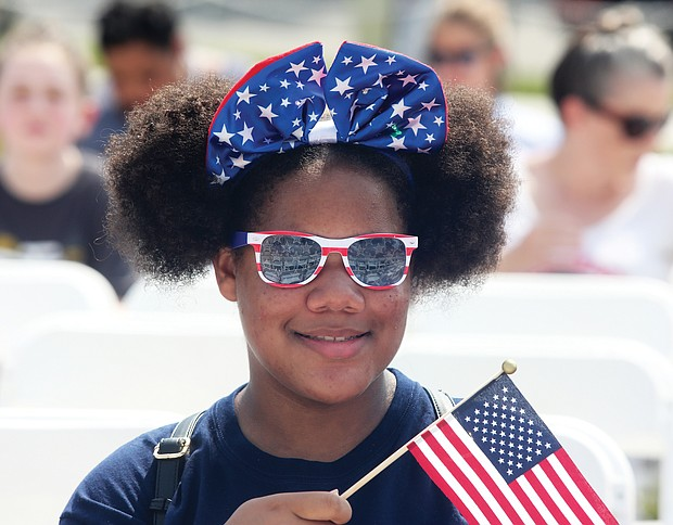 Star-Spangled Celebration: A youngster with Deborah De Los Santos' summer camp group waves Old Glory at the Fourth of July ceremony to swear in new U.S. citizens at the Virginia Museum of History & Culture on Richmond's Arthur Ashe Boulevard. (Regina H. Boone/Richmond Free Press)