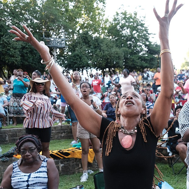 Pam Kearny joins in the praise as one of the hundreds of people attending the 10th Annual Gospel Music Festival on Sunday at Dogwood Dell. The free event was hosted by Sheilah Belle and Praise 104.7 FM as part of the City of Richmond's Festival of Arts. (Sandra Sellars/Richmond Free Press)