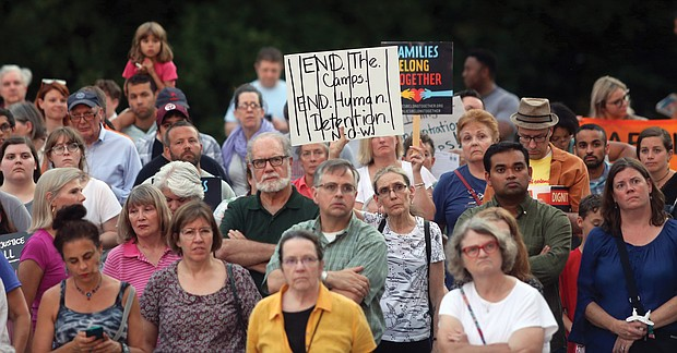 """A crowded scene from last Friday's """"Lights for Liberty"""" vigil on the State Capitol grounds calling for an end to the detention camps and family separations imposed on migrants to the United States along the southern border. Hundreds of people attended the vigil, which was sponsored by numerous Richmond area organizations, including Indivisible Virginia, the Virginia ACLU, UndocuRams and ReEstablish Richmond. Local activists, advocates and others spoke at the event, which was one of nearly 700 Lights for Liberty events held around the globe. Bridgette Newberry, an art teacher in Richmond, held her sign aloft in the crowd. (Regina H. Boone/Richmond Free Press)"""