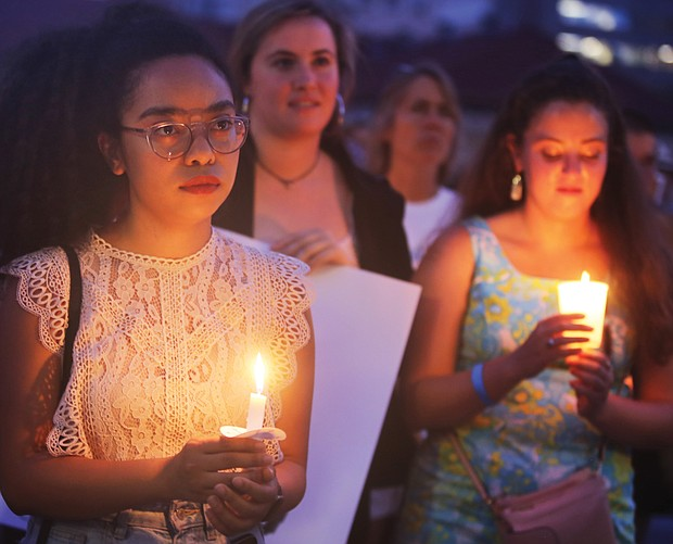 """Adele McClure, left, holds a candle during last Friday's """"Lights for Liberty"""" vigil on the State Capitol grounds calling for an end to the detention camps and family separations imposed on migrants to the United States along the southern border. Hundreds of people attended the vigil, which was sponsored by numerous Richmond area organizations, including Indivisible Virginia, the Virginia ACLU, UndocuRams and ReEstablish Richmond. Local activists, advocates and others spoke at the event, which was one of nearly 700 Lights for Liberty events held around the globe. (Regina H. Boone/Richmond Free Press)"""