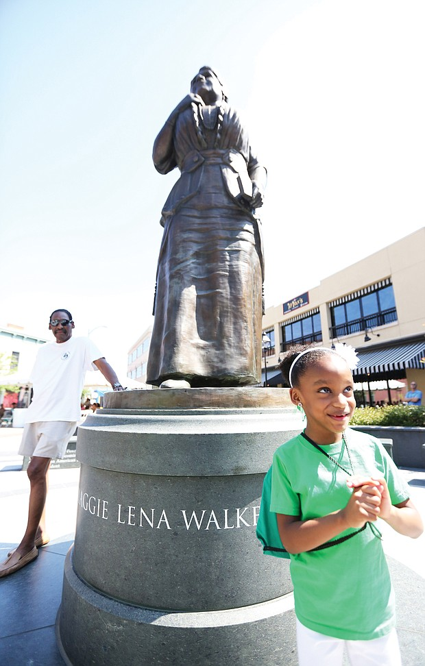 Lyla Hopkins-Hawkins, 6, stands at the foot of the statue of noted Richmond businesswoman and activist Maggie L. Walker at Broad and Adams streets in Downtown during last Saturday's commemoration of Mrs. Walker's 155th birthday. The young- ster attended the event with her grandfather, J. Maurice Hopkins, a 1965 graduate of Maggie L. Walker High School who helped push the effort to erect the statue. Also attending the event is Dr. Johnny Mickens III, left, Mrs. Walker's great-grandson. (Regina H. Boone/Richmond Free Press)